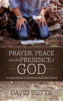 Man in blue jeans and blue flannel shirt with bracelet on right arm and watch on the other arm is kneeling in prayer with Bible on ground in wooded area for peace and the presence of God.