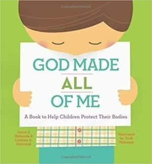 Little girl holding a sign that says God Made All Of Me with a green background.