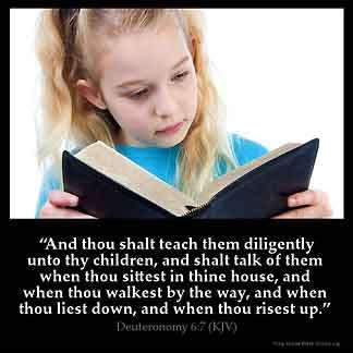 Little girl with long hair in pony tail wearing blue shirt sitting at desk reading the Bible, Deuteronomy-6-7.