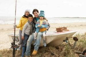 Family of four setting on boat with fishing poles getting ready to go fishing signifying Family Matters.