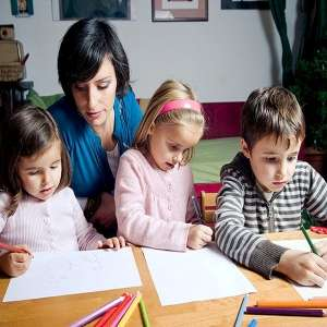 Mom homeschooling her 2 children at kitchen table.