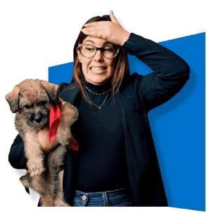 Lady standing up wearing black sweater holding her small dog under her arm ready to start Dog Training.