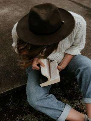 A young girl sitting on ground with jeans, white sweater, dark brown hat reading Bible for inspiration.