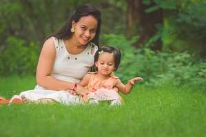 Mama and daughter sitting on the grass in front of wooded area.