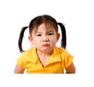 Angry little girl with black pony tales and yellow shirt