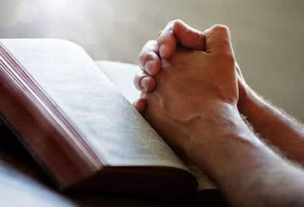 Open Bible on desk with a man's hands in praying position over Bible stating in black letters Let's Pray, Talking to God with the Words of the Bible.