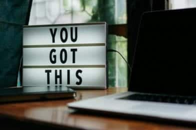 A electic sign sitting on a desk with laptop computer showing You Got This.